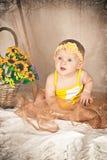 Bebé que se sienta y que parece para arriba asombrado Imagen de archivo