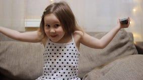 Beb? que ve la TV El niño gira la televisión usando el telecontrol almacen de metraje de vídeo