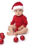 Bebê que veste um chapéu de Santa Claus, jogando com bolas vermelhas Imagem de Stock Royalty Free