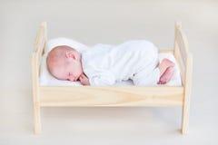 Bebé recién nacido durmiente lindo en una cama del juguete Imagenes de archivo