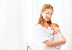 Bebé recién nacido en el abrazo blando de la madre Foto de archivo