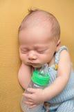 Bebé recién nacido que duerme con la botella Foto de archivo