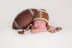 Bebé recién nacido que lleva un sombrero hecho a ganchillo del fútbol Fotos de archivo libres de regalías