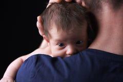 Bebé recién nacido que miente en el hombro del padre Foto de archivo