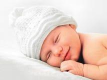 Bebé recién nacido sonriente en el cierre blanco del sombrero para arriba Imagenes de archivo