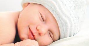 Bebé recién nacido sonriente en el sombrero blanco Fotos de archivo libres de regalías