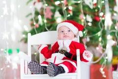 Bebê recém-nascido pequeno no traje de Santa sob a árvore de Natal Imagem de Stock