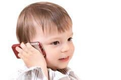 Bebé sonriente con el teléfono móvil Imagen de archivo libre de regalías