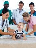 Bebé sonriente con personas médicas en hospital Imagen de archivo libre de regalías