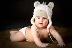 Bebé sonriente en casquillo del oso Imagen de archivo libre de regalías