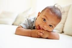 Bebé sonriente que miente en la panza en casa Foto de archivo libre de regalías