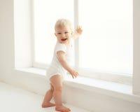 Bebé sonriente que se coloca en el sitio blanco en casa Imagen de archivo libre de regalías