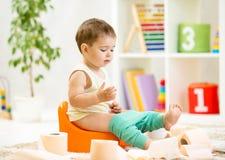 Bebé sonriente que se sienta en el pote de cámara con el retrete Foto de archivo libre de regalías