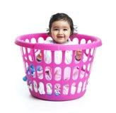 Bebé sonriente que se sienta en la cesta de lavadero Foto de archivo