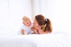 Bebé y madre en cama Imágenes de archivo libres de regalías