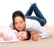 Bebé y madre que mienten en la alfombra beige junto Foto de archivo libre de regalías
