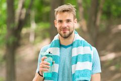 Beba alguma água O basculador do homem com a toalha em ombros guarda a garrafa de água Refrescamento da roupa do esporte do atlet Fotografia de Stock