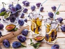 Beba de ciruelos frescos en un fondo de madera con un vidrio goble Foto de archivo libre de regalías