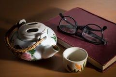 Beba el té con el libro, el pote y la taza de lectura con inmóvil Imagen de archivo libre de regalías