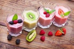 Beba la fresa del verano de los smoothies, zarzamora, frambuesa en la tabla de madera fotos de archivo