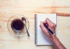 Beba o café e escreva-o no caderno Foto de Stock Royalty Free