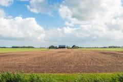 Bebauter Boden vor einem modernen niederländischen Bauernhaus mit Scheunen Lizenzfreies Stockbild