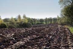 Bebautes landwirtschaftliches Feld, Frühlingsvorarbeit für das Säen und Pflanzen Lizenzfreie Stockfotografie