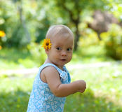 Bebe. The small child costs on a glade with a flower behind an ear Stock Image