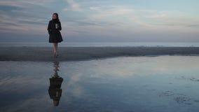 Beber da jovem mulher leva embora o ar livre do caf? em uma praia durante um por do sol azul frio com reflex?o clara na ?gua sobr video estoque