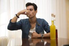 Beber de assento do homem novo apenas em uma tabela com as duas garrafas do licor Foto de Stock Royalty Free