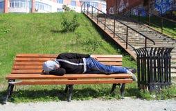 Bebió restos del hombre en un banco en parque fotos de archivo