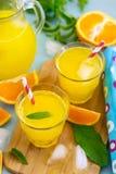 Bebida alaranjada doce com as folhas do gelo e de hortelã foto de stock royalty free