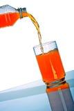 Bebida alaranjada que derrama no vidro do frasco plástico Foto de Stock Royalty Free