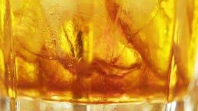 Bebida alcohólica con los cubos de hielo en vidrio fresco almacen de video