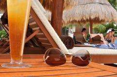 Bebida alcohólica y gafas de sol por una piscina tropical Fotos de archivo