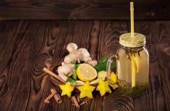 Bebida amarilla dulce en un tarro de cristal del albañil grande con el limón, el canela, la menta, el jengibre, y el carambola en Foto de archivo libre de regalías