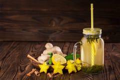 Bebida amarilla dulce en un tarro de cristal grande con el limón, el canela, la menta, el jengibre, y el carambola en un fondo de Imagenes de archivo