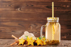 Bebida amarilla en un tarro de albañil grande con la paja al lado del limón, del canela, del jengibre, y del carambola cortados e Imágenes de archivo libres de regalías