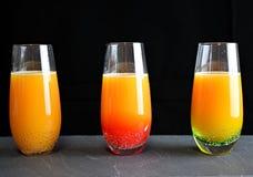Bebida anaranjada en vasos de medida fotografía de archivo libre de regalías