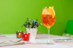 Bebida anaranjada en vidrio en fondo verde Imagenes de archivo