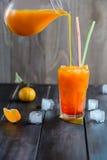 Bebida anaranjada fresca del cóctel con los cubos de hielo imagenes de archivo