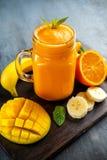 Bebida anaranjada fresca del smoothie con el plátano, mango, zanahorias en el tablero de madera negro fotografía de archivo