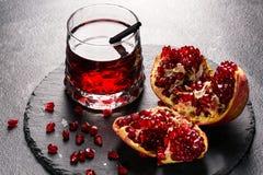 Bebida brilhante da grandada e uma romã vermelha em uma luz - fundo cinzento Exotic ingredients for summer cocktails Saudável foto de stock royalty free