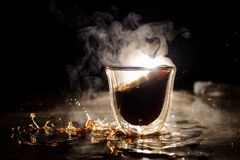 Bebida caliente desbordada del café de la taza de cristal fotografía de archivo libre de regalías