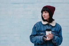 Bebida caliente sonriente joven del inconformista de la muchacha a disposición, en un fondo ligero Foto de archivo libre de regalías