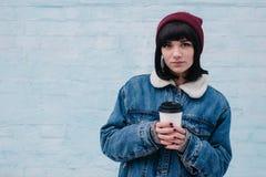 Bebida caliente sonriente joven del inconformista de la muchacha a disposición, en un fondo ligero Imagen de archivo libre de regalías