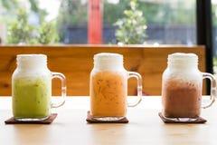 Bebida colorida do chá do leite na tabela de madeira Fotografia de Stock