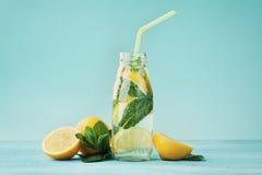 Bebida da limonada da água de soda, do limão e da hortelã no frasco no fundo de turquesa imagem de stock