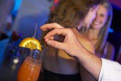 Bebida da mulher drogando-se do homem na barra fotos de stock