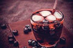 Bebida da uva-do-monte com as bagas e os cubos de gelo Fotografia de Stock